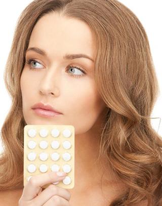 Девушка держит гормональные контрацептивы в руке